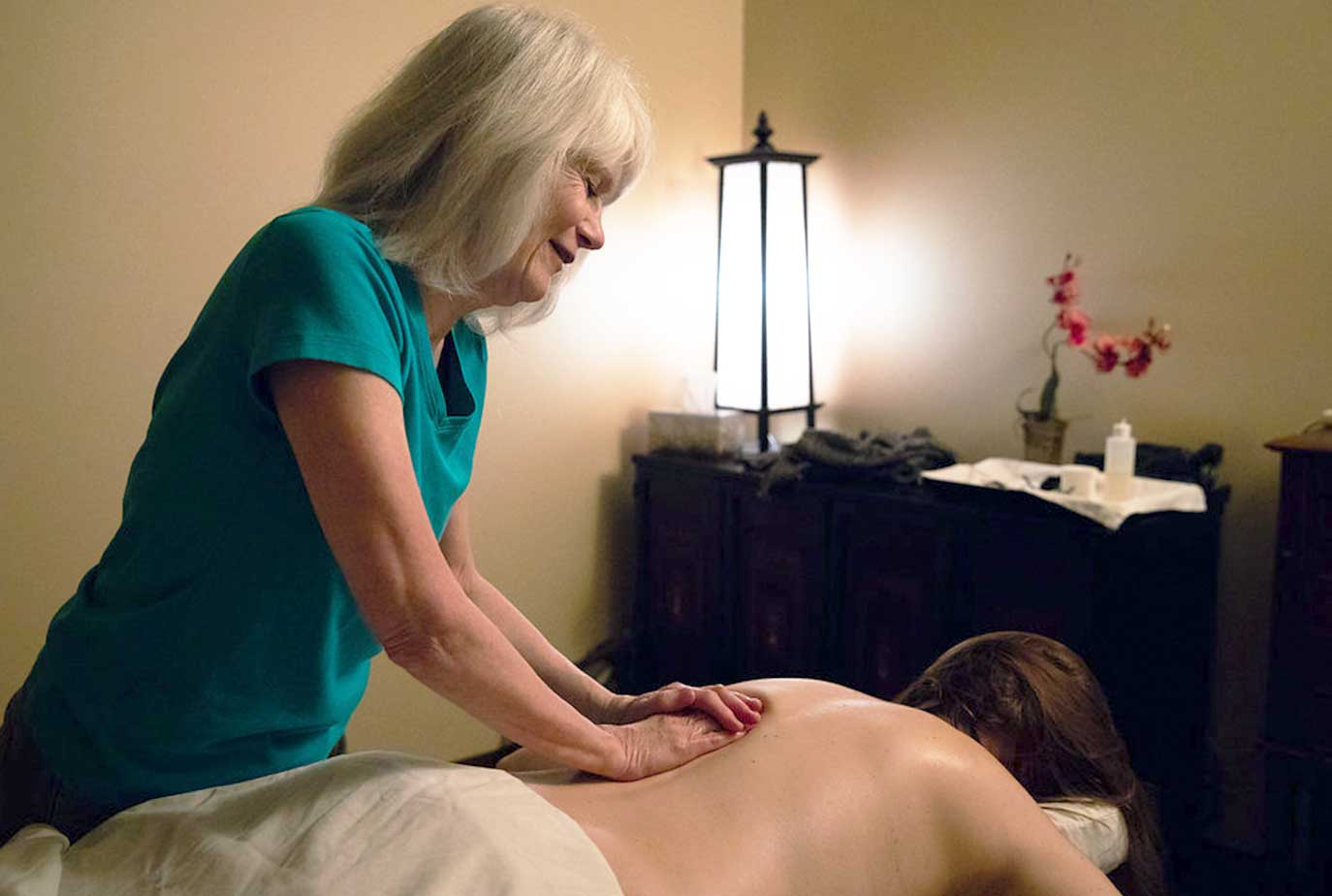 Woman in Blue scrubs massaging woman Massage Therapy Works Inc in Somerville, MA